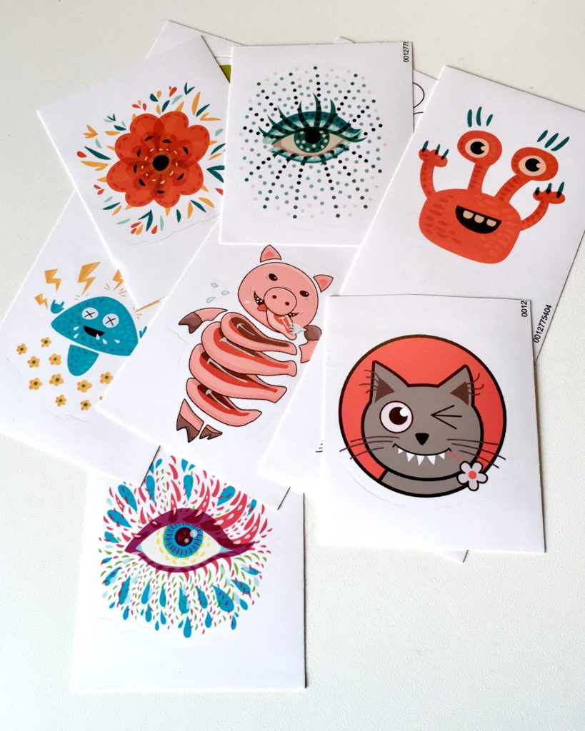 Art stickers which I bought from my Redbubble store - heavy metal mushroom, orange flower, orange monster, pig cute in steaks, winking kitty cat and psychedelic blue eye.